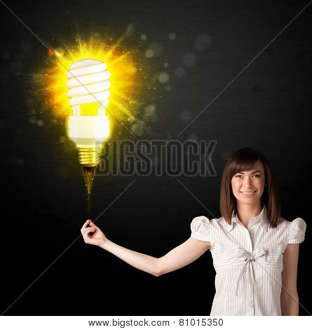 Businesswoman hold a shining eco-friendly idea bulb on a black background