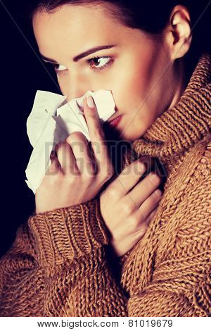 Young beautiful woman with tissue. On black background.
