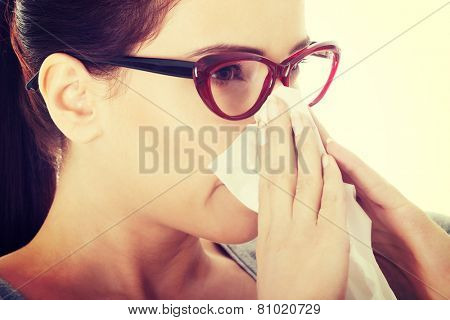 Young beautiful woman with tissue having runny nose.