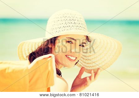 Beautiful young woman in a hat and swimsuit over seaside sunny day.