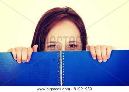 Beautiful woman behind blue workbook.