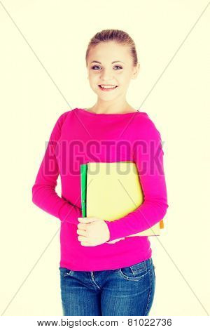 Young student woman holding workbook.