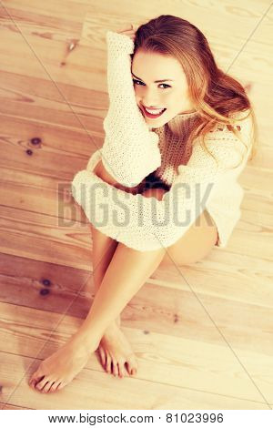 Picture of a careless young caucasian woman on the wooden floor.