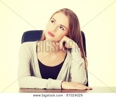 Beautiful casual woman sitting by a desk and day- dreaming.
