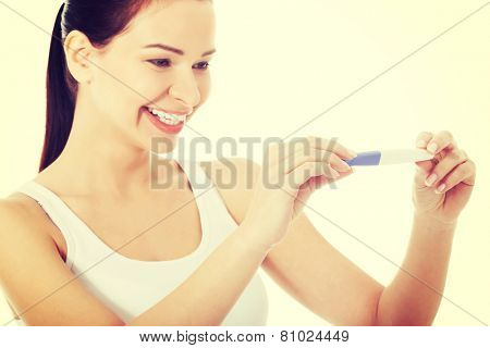 Happy smiling woman with positive pregnancy test.