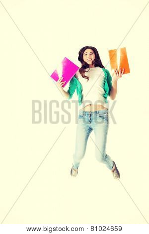 Young beautiful student jumping with files, workbook.