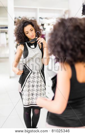Woman shopping fashion, trying on dress in store