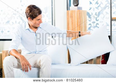 Man buying sofa in furniture store showroom