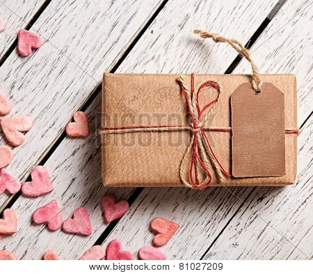 Vintage gift box with blank gift tag and heap of small hearts on white wooden background.