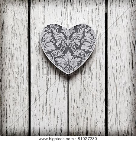 Heart shaped Valentines Day gift box on white wood table.