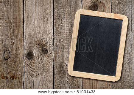 Small Blackboard On Wooden Background