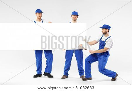 Three delivery men holding empty board