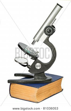 Microscope Standing On The Thick Old Book Isolated On White