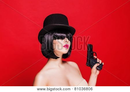 fashion beautiful model with pistol in hat cylinder, on red background