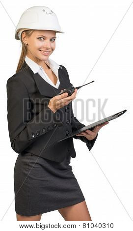 Businesswoman wearing hard hat holding clipboard and walkie talkie