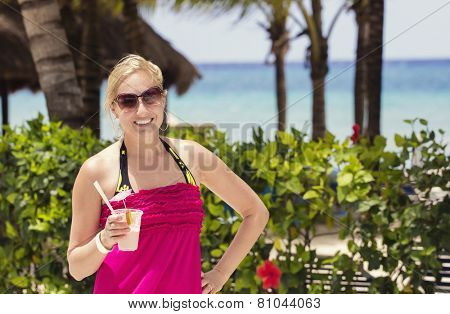 Woman enjoying a cocktail drink by the beach