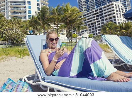 Woman talking on her cell phone while lounging on the beach