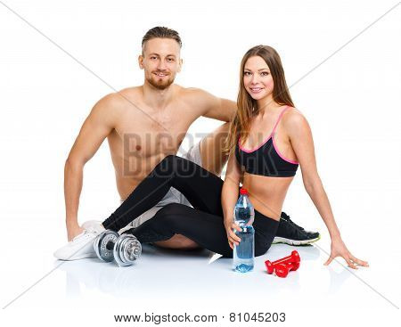 Athletic Couple - Man And Woman After Fitness Exercise Sitting With Dumbbells On The White