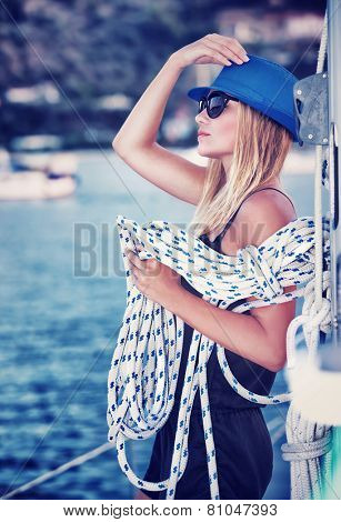 Sexy girl standing on sailboat with rope, vintage style photo of attractive sailor girl, active lifestyle, summer vacation concept