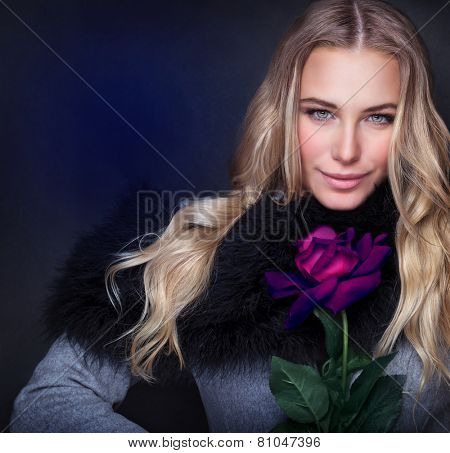 Portrait of sexy attractive woman wearing stylish coat holding in hand beautiful purple rose isolated on dark blue background, happy Valentine day, style and fashion concept
