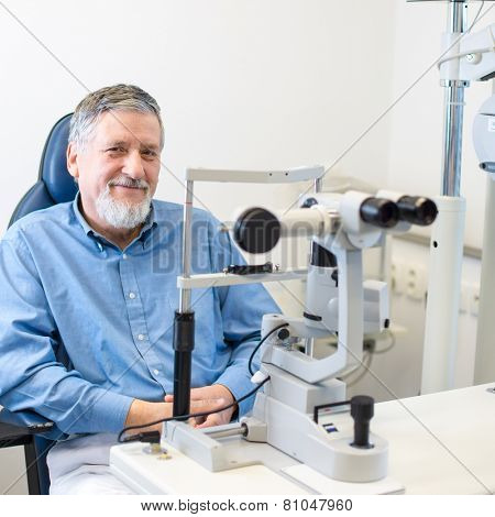 Optometry concept - Senior patient sitting the exmanination chair , before having his eyes examined by an eye doctor, smiling, looking happy