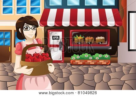 Female Store Owner Standing In Front Of Her Store Carrying A Basket Of Apples
