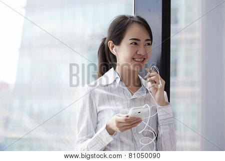 Asian Business Woman Conference With In-ear Headphone In The Office.