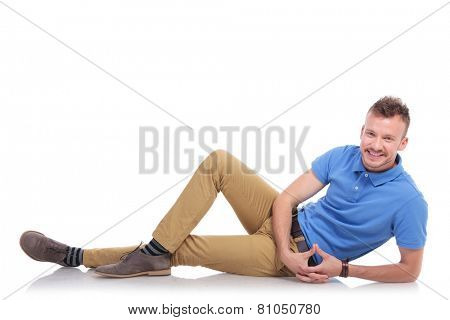 full length picture of a casual young man lying on the floor and smiling for the camera. on a white background
