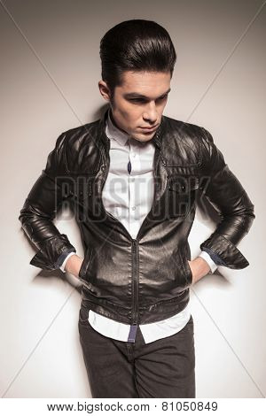 fashion man leaning on a white wall holding his hands in pockets while looking down.