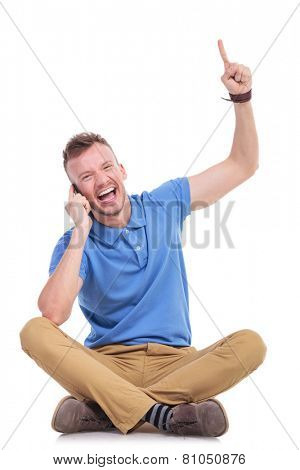 casual young man sitting on the floor with his legs crossed and talking on the phone while pointing upwards and smiling for the camera. isolated on white