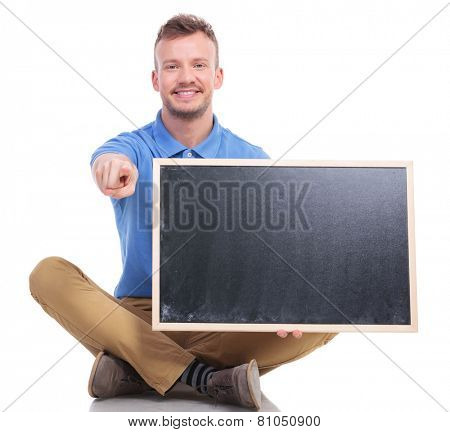 picture of a casual young man sitting on the floor with his feet crossed while holding a small blackboard and pointing at the camera with a smile on his face. on a white background