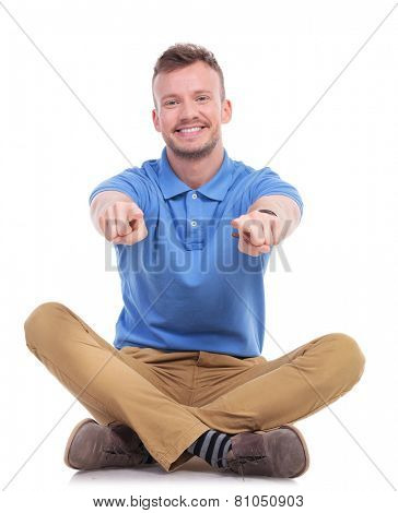 casual young man sitting on the floor with his legs crossed and pointing at the camera with both hands. isolated on white