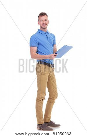 full length portrait of a casual young man taking some notes on a clipboard and smiling for the camera. on a white background