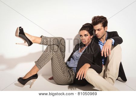 Fashion couple sitting on the floor together, looking away from the camera. The woman is leaning on ther man.