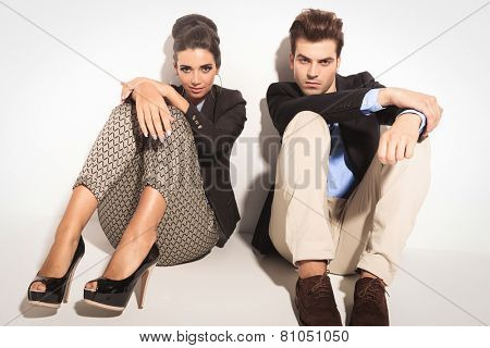 Fashion couple sitting on studio background with the knees up, holding their hands on them.