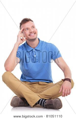 casual young man sitting on the floor with his legs crossed and thinking while looking away with a smile on his face. isolated on white