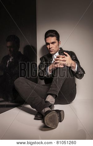 Attractive young casual man looking away from the camera while sitting on the floor holding his knee with both hands.