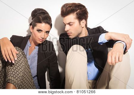 Gorgeous fashion woman sitting on the floor, looking at the camera while her boyfriend is looking at her.