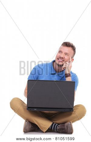 casual young man holding his laptop while sitting on the floor with his feet crossed and looking away in a pensive manner. on a white background