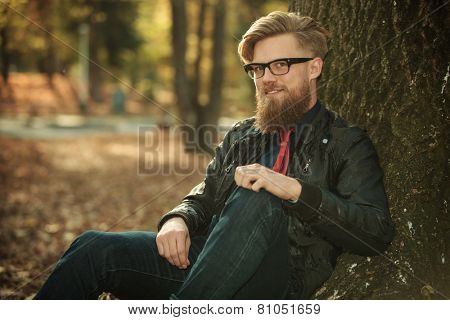 Similing young fashion man looking at the camera while leaning on a tree in the park.