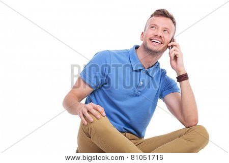 casual young man sitting on the floor with his legs crossed and talking on the phone while looking away from the camera, with a smile on his face. isolated on white