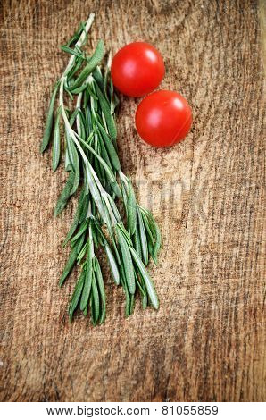 Sprigs Of Rosemary And Two Cherry Tomatoes On A Wooden Board Top View Vertical
