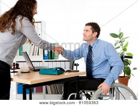 Man In Wheelchair Is Greeting A Woman