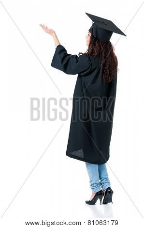Beautiful graduate girl student in mantle showing something, isolated on white background