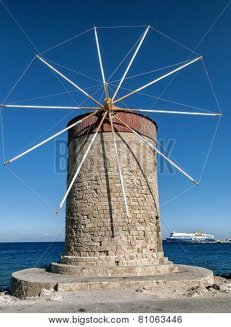 A Stone Retro Windmill On Background Of Blue Sea