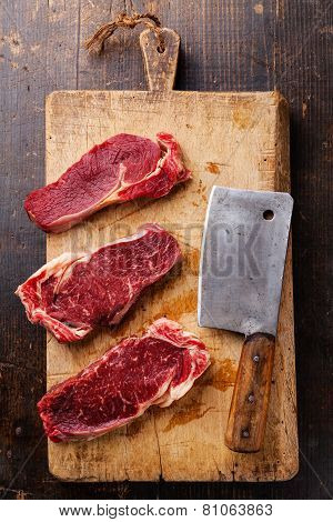 Raw Fresh Meat Ribeye Steak Entrecote And Meat Cleaver On Cutting Board On Wooden Background
