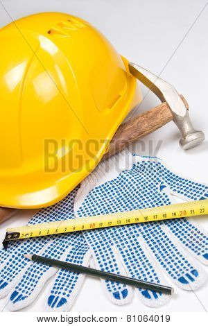 Close Up Of Builder's Tools - Helmet, Work Gloves, Hammer, Pen And Measure Tape Over White