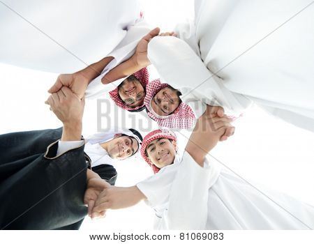 Happy group of Arabic people with heads together in circle over sky background