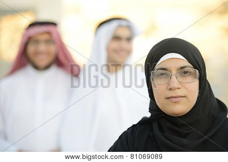 Arabic Muslim businesswoman leading group of Middle eastern Gulf people