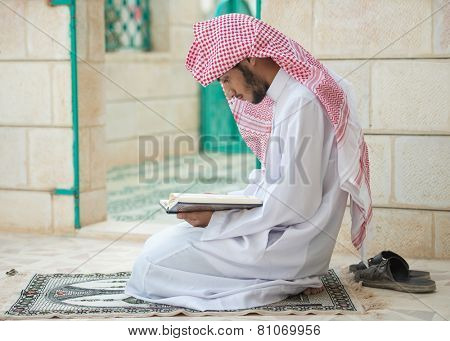 Young Arabic Muslim man reading Koran and praying